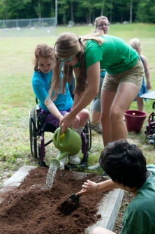 Learning to garden - FLEX participants plant and water seeds.